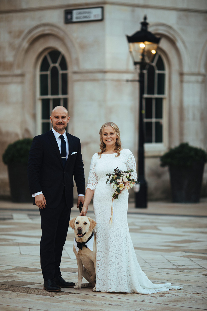 Bride and groom with their pet labrador on their wedding day