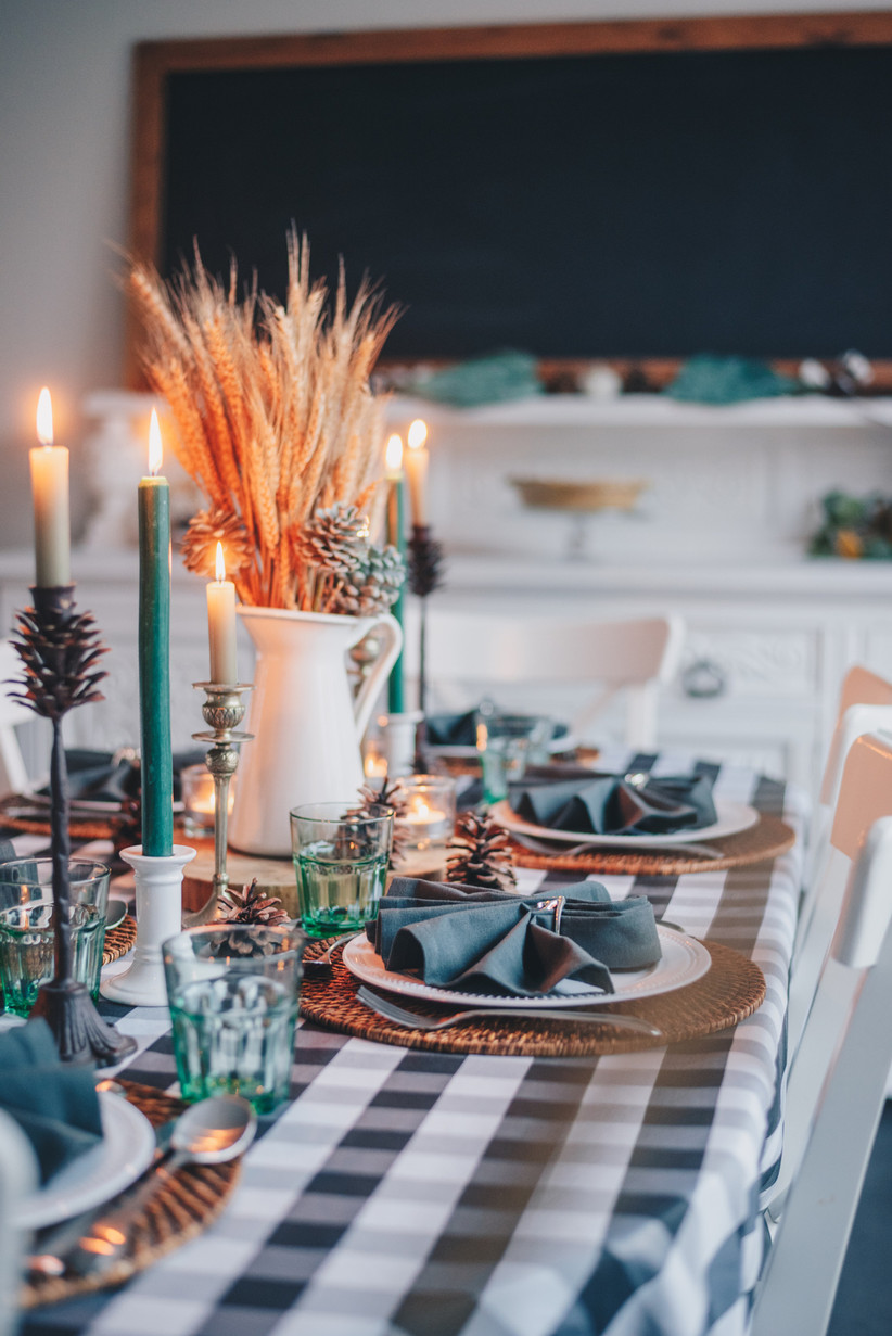 Dark green themed tablescape with a checked tablecloth, dark green lit candles, dark green napkins, raffia place settings and pine cone decoration