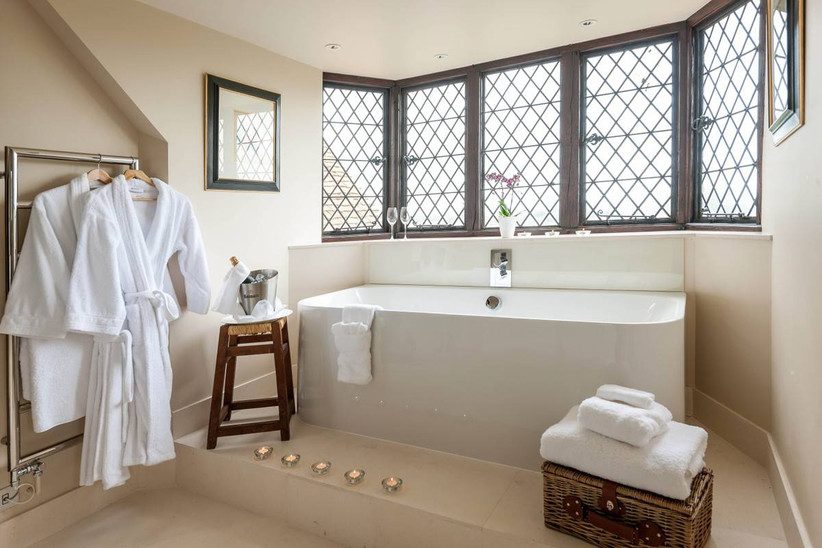 White bathroom with robes hanging up and a champagne bottle