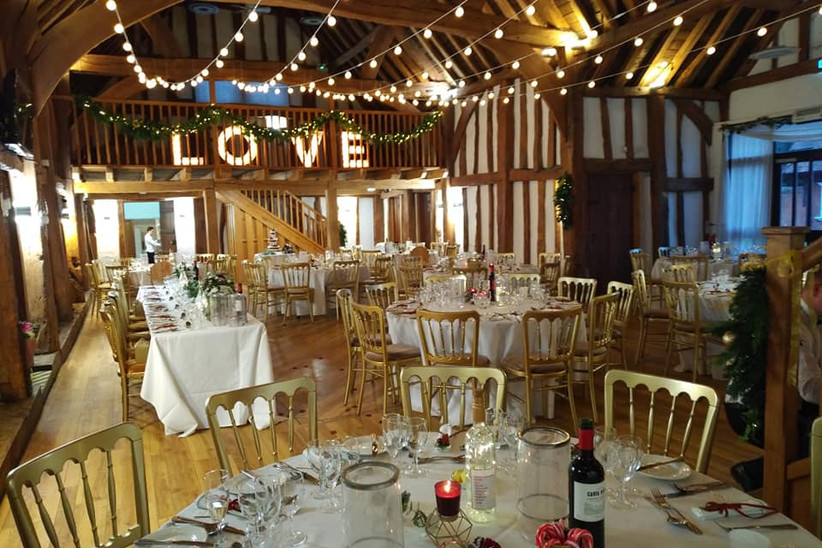 Interior of the Tudor Barn dressed for a wedding with festoon lights and a light-up love sign