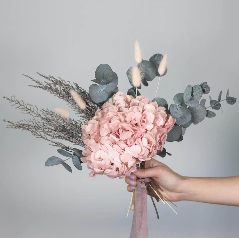 White woman with a lilac manicure holding a bunch of light pink and green preserved flowers tied with a light pink ribbon