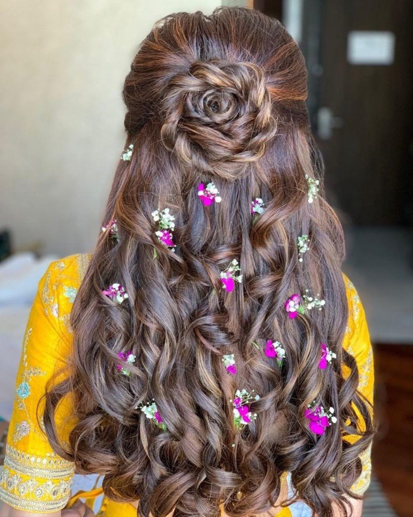 Curled rose half up half down hairstyle with real flowers