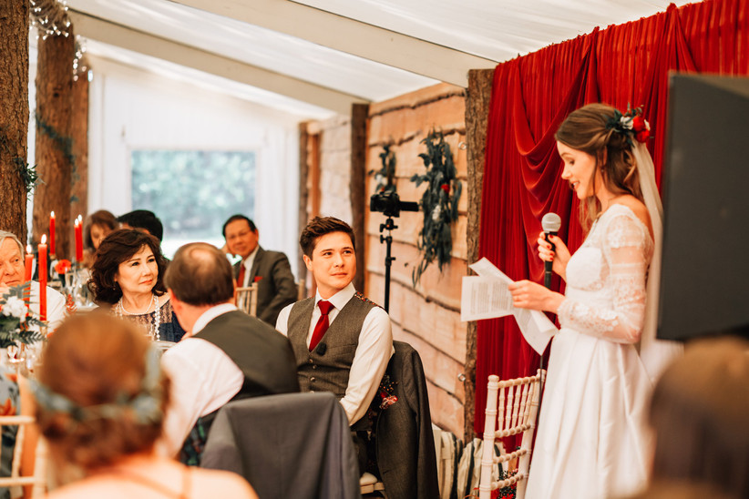 Bride reading a speech with a microphone against a red backdrop with groom and wedding guests looking on