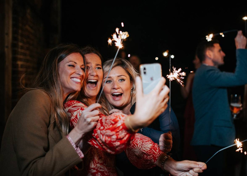 Three girls laugh and take a selfie with sparklers