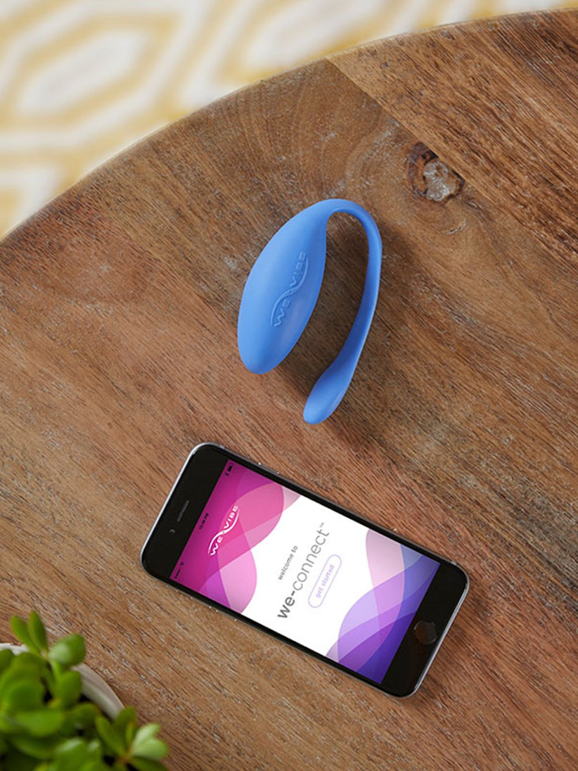 A blue curved vibrator on a wooden table next to a smartphone displaying the We Vibe app on the screen