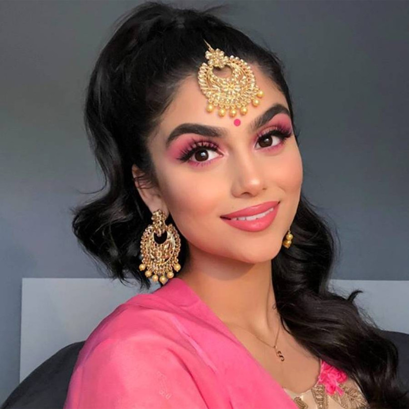 Girl with gold accessories, pink outfit and pink eyeshadow