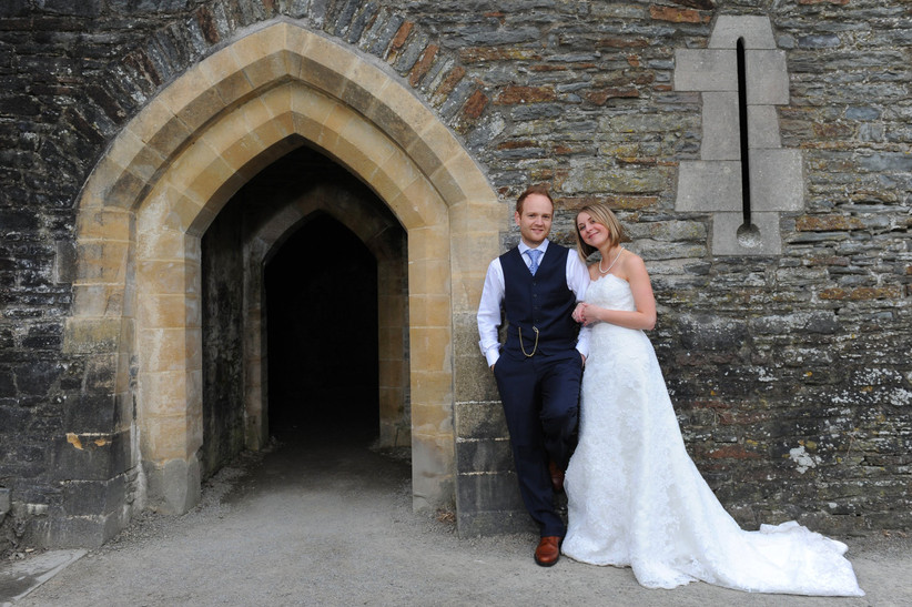 White bride with a blonde bob wearing a strapless white wedding dress links arm with a white groom in a waistcoat suit in front of a castle door
