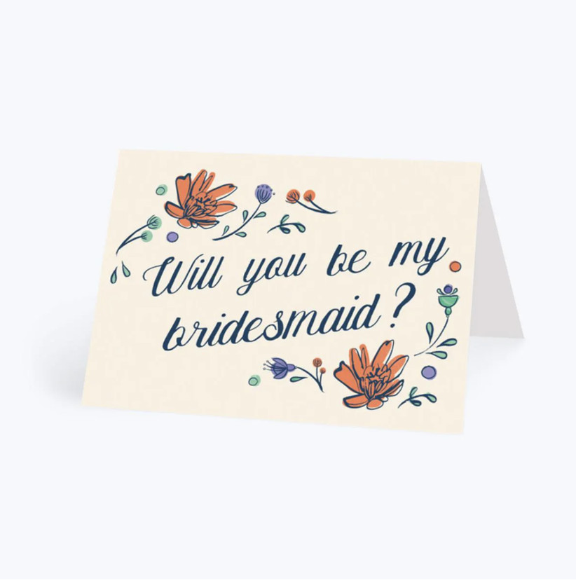 Cream card with floral illustration and will you be my bridesmaid written in calligraphy in the centre