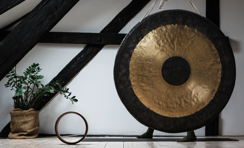 Person behind a large gold and black gong with a yoga mat and yoga circle next to it and a green plant in the corner of the room