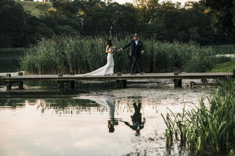 Bride and groom walking up wooden decking on a lake