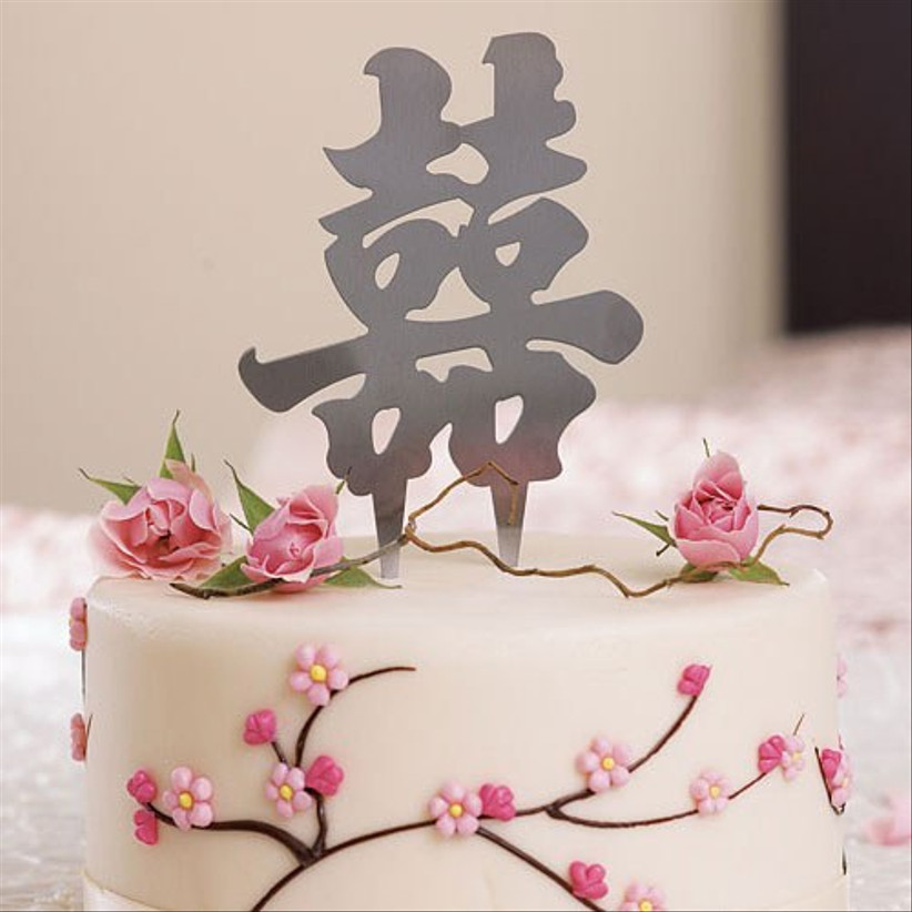 Chinese double happiness symbol wedding cake topper on a cherry blossom decorated cake