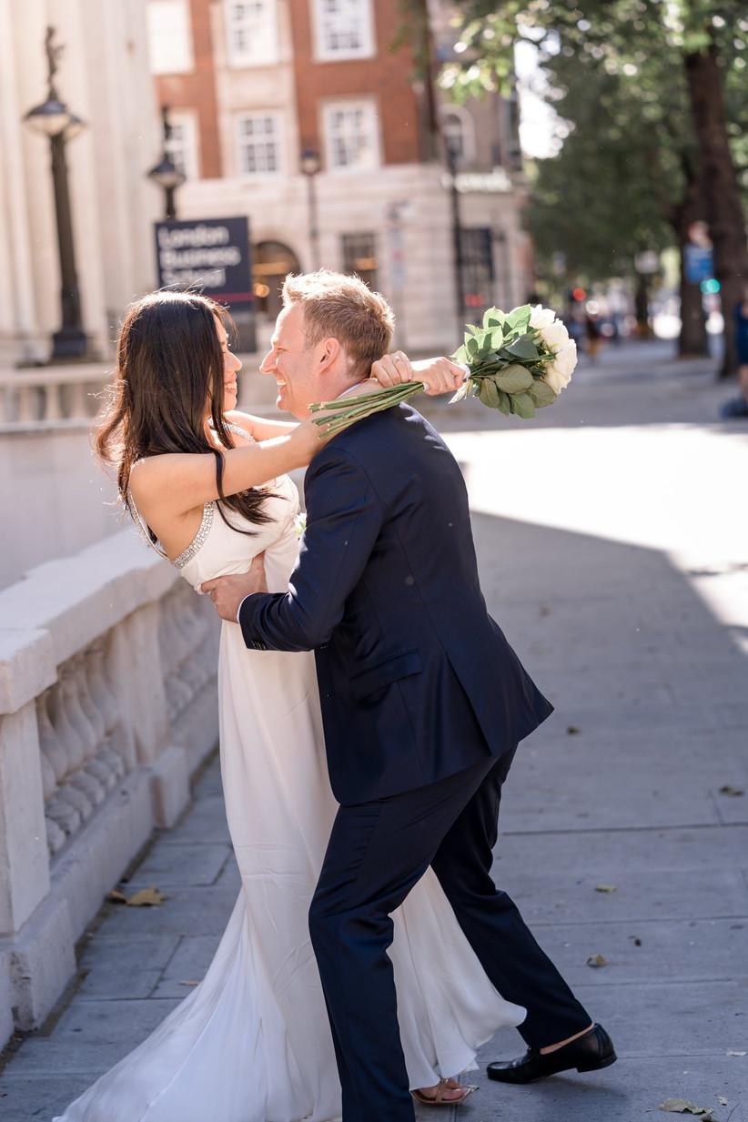 Groom embracing bride on a London street