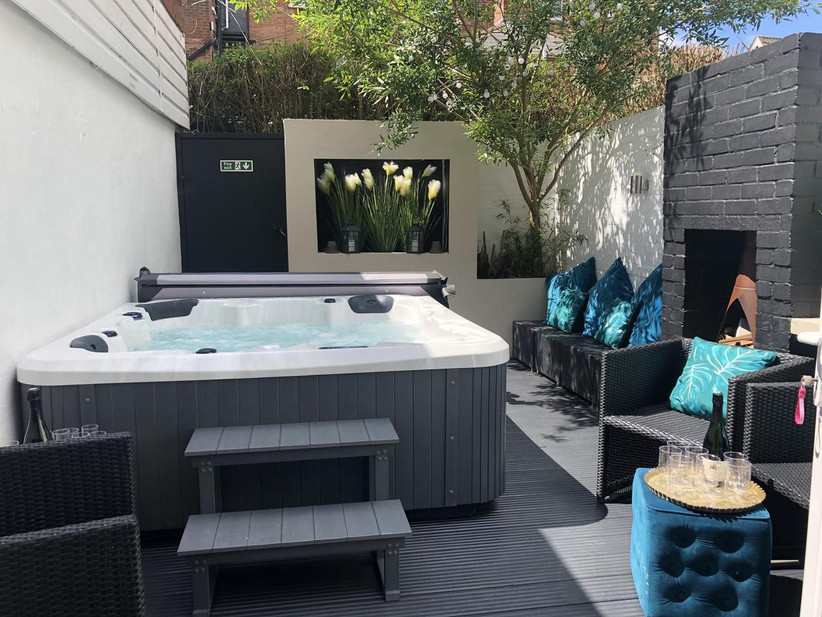 Outside patio with hot tub and black chairs with palm tree cushions