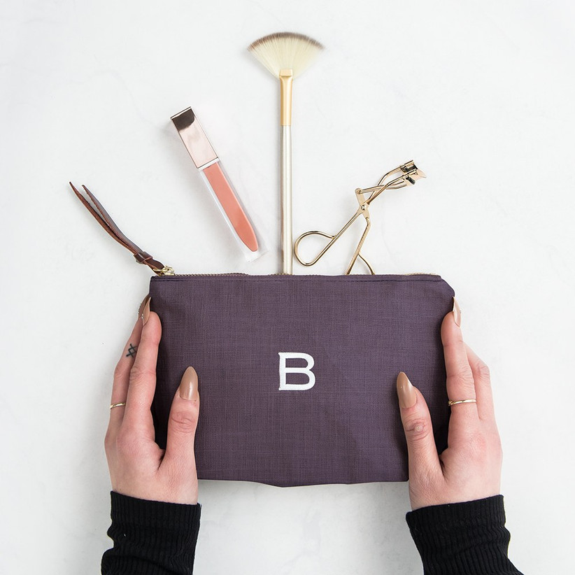 White woman with a nude manicure, rings and tattoos holding a navy personalised linen makeup bag with a lipgloss, eyelash curler and gold pencil spilling out of the top