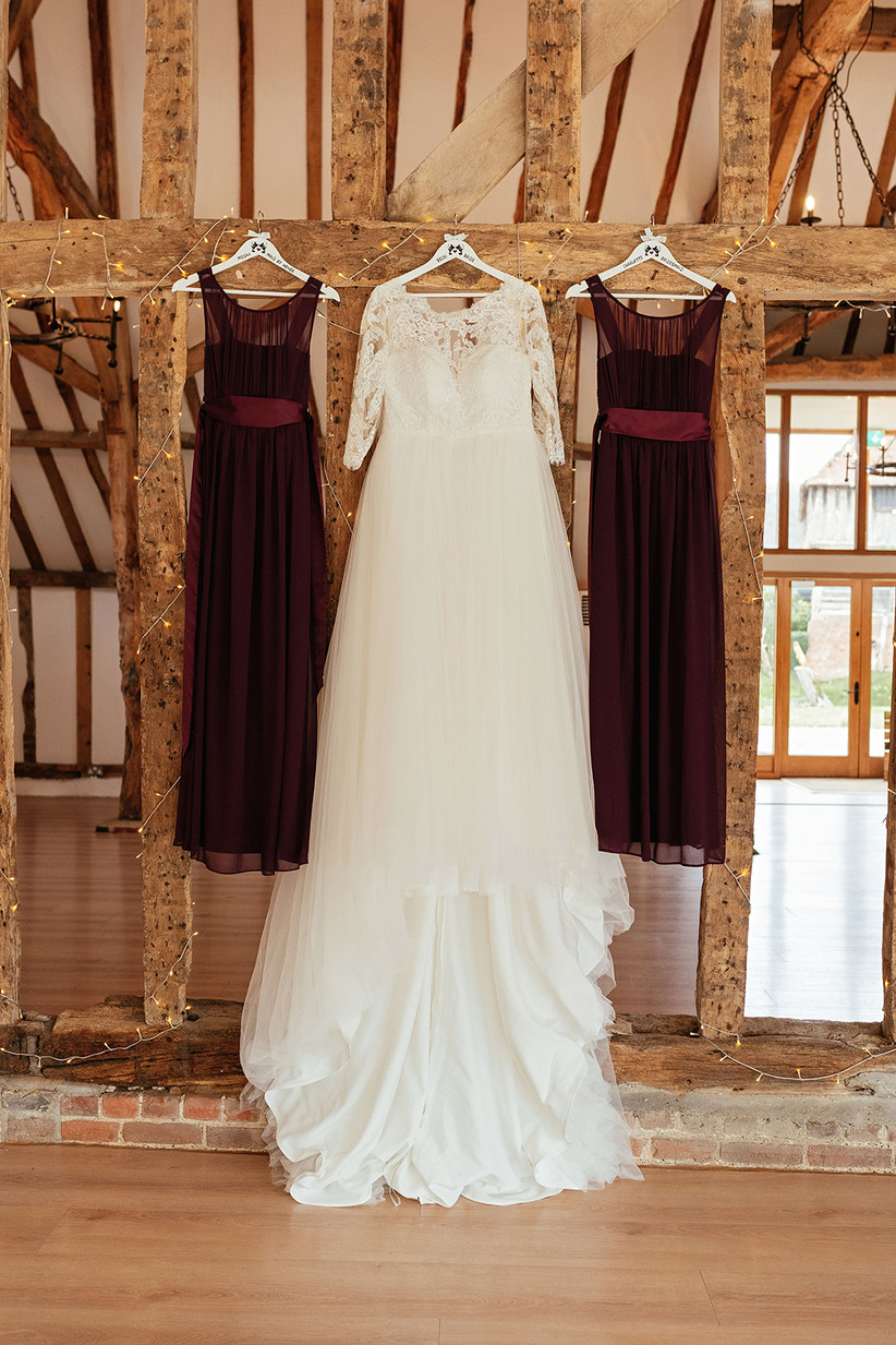 White wedding dress and burgundy bridesmaids' dresses hanging from oak beams