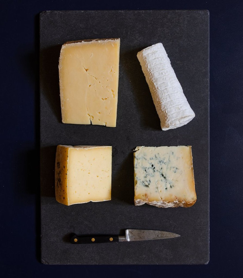 Slab of slate on a navy tablecloth with four different cheeses and a sharp knife