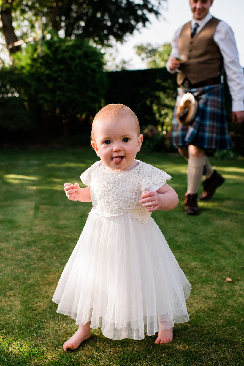 Caitlin and Stephen's baby daughter in a white flower girl dress