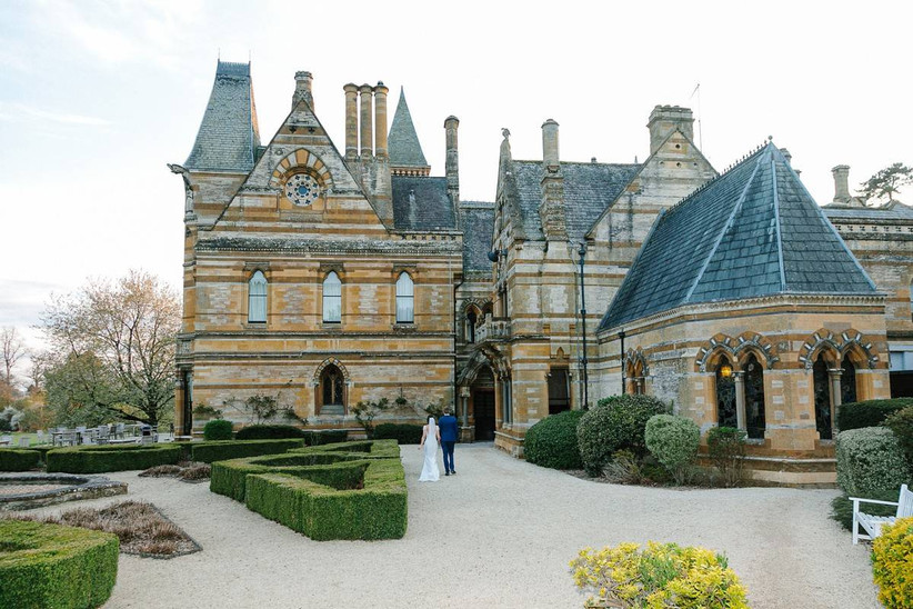 Bride and groom walk towards a gothic mansion