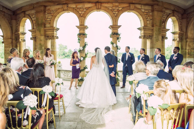 Bride and groom marry in a ceremony under stone arches