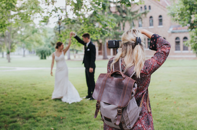 A female photographer taking a photo of a bride and groom
