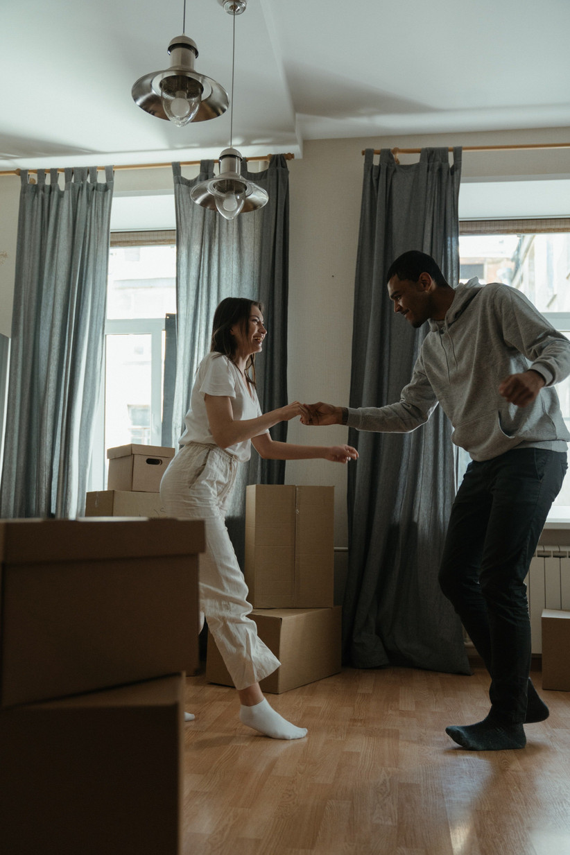 couple dancing in new home around cardboard boxes