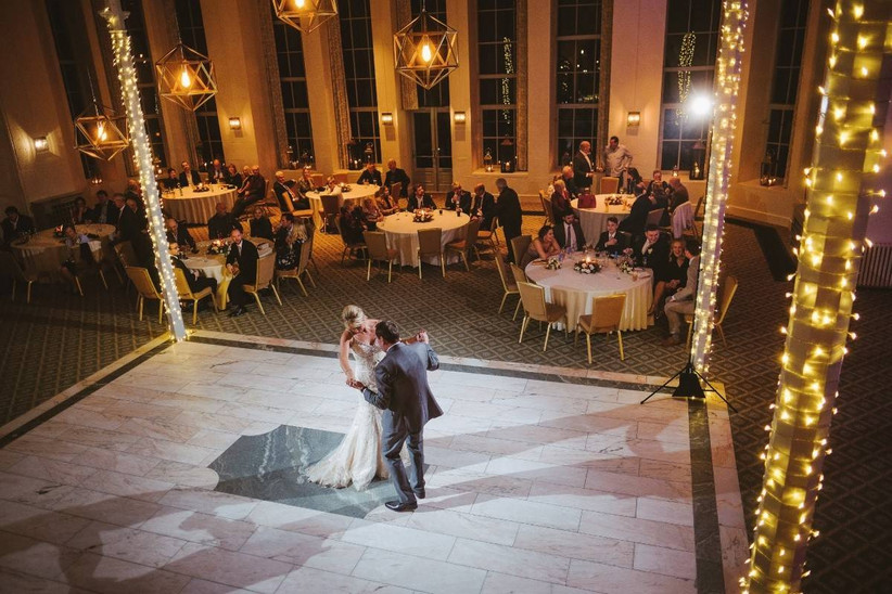 Bride and groom have their first dance in a fairy light lit hall