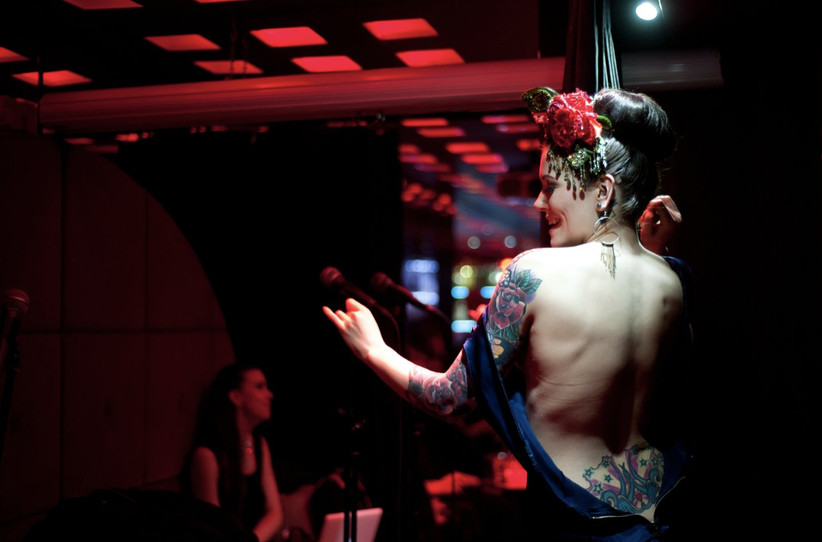 A white woman with tattoos and a red rose in her hair performing a burlesque show in a red lit club