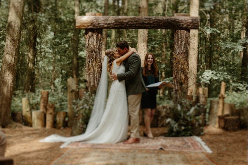 Bride and groom kiss at a woodland wedding ceremony