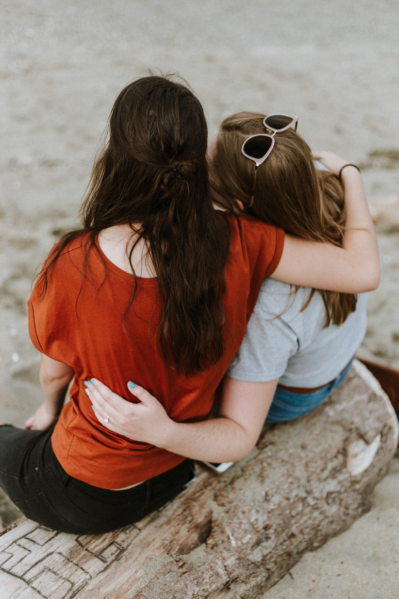 Female couple from behind with their arms around each other in a supportive post