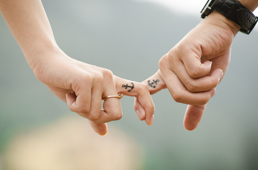 Couple with matching tattoos linking fingers to show they're soulmates
