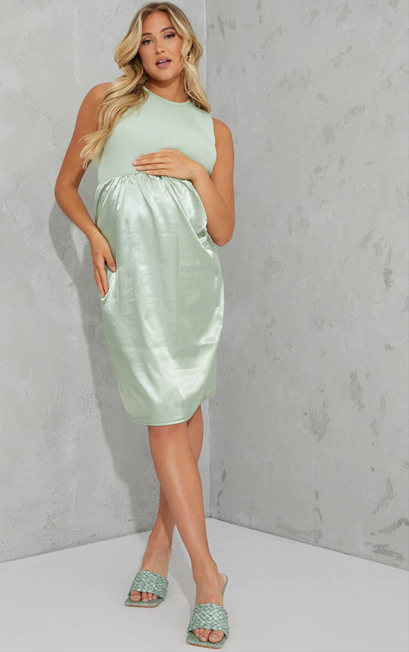 Pregnant model wearing a green skirt and bodysuit