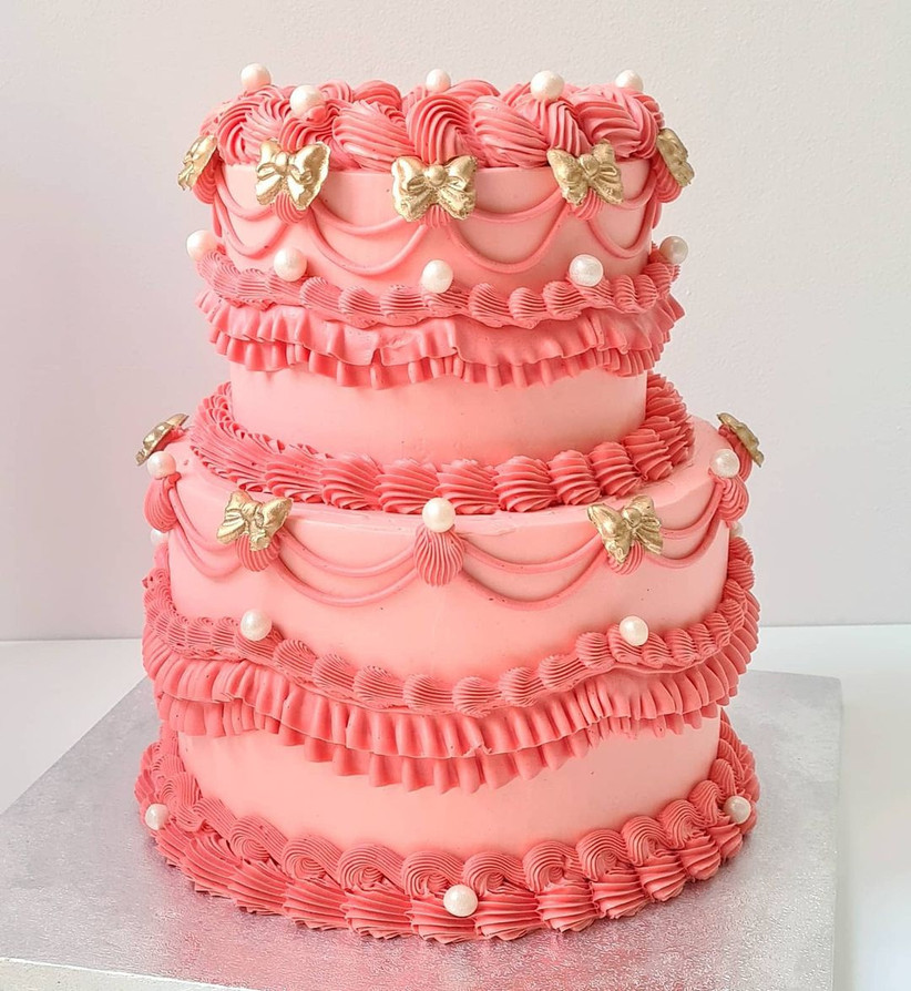 Bright pink tiered wedding cake with frills, bows and pearls