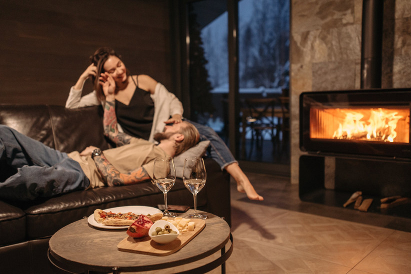Couple lying together by a fire with wine