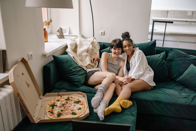 A female couple snuggle up on the sofa with a pizza on the table in front of them
