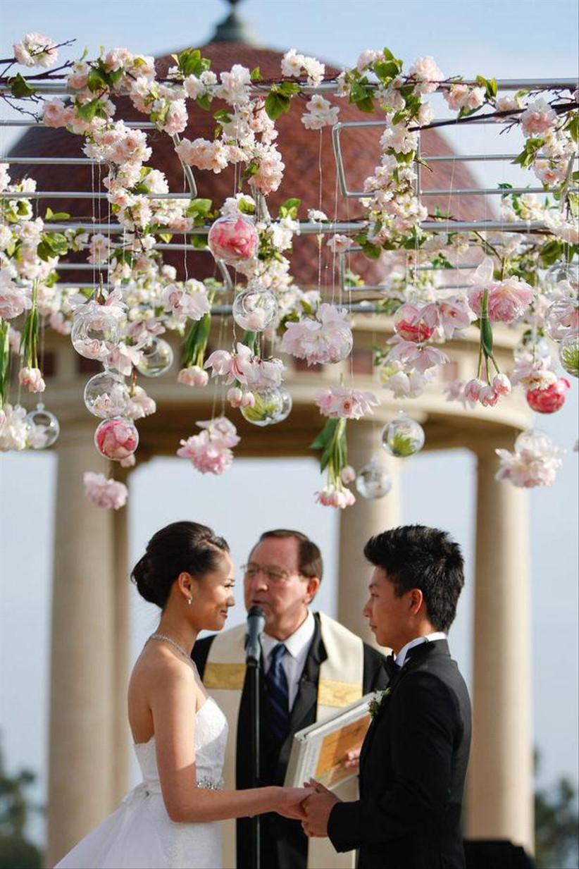 Bride and groom exchange vows under hanging flowers