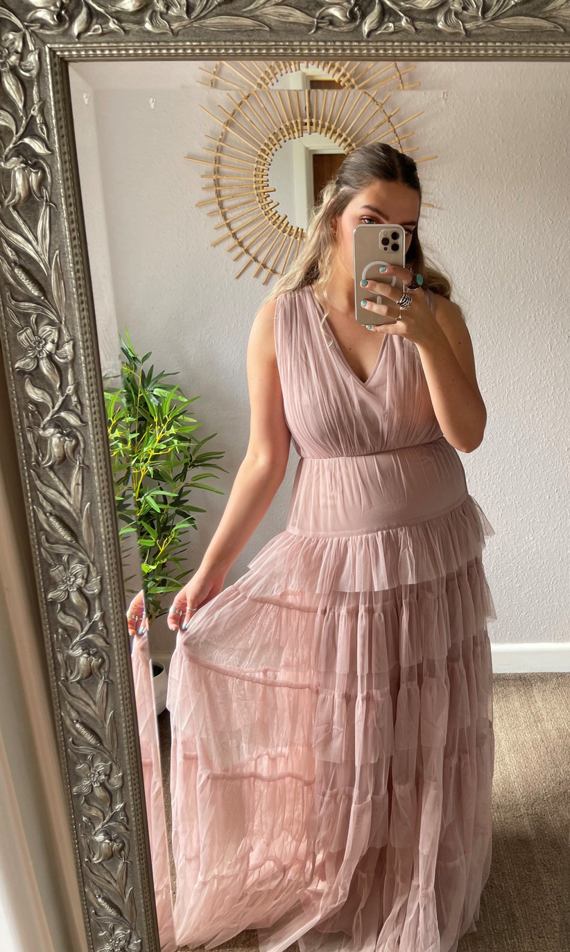 Model wearing a pink ruffle bridesmaid dress