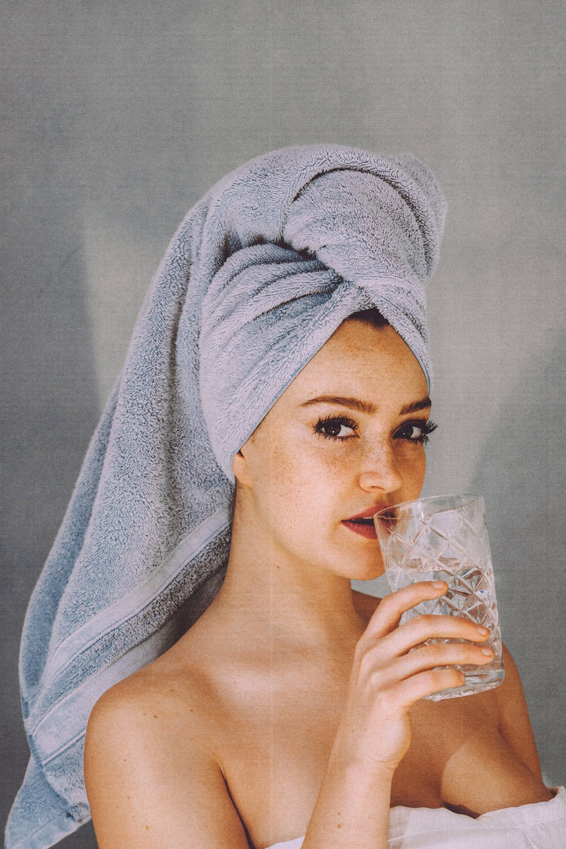 Girl with hair in a towel drinking water