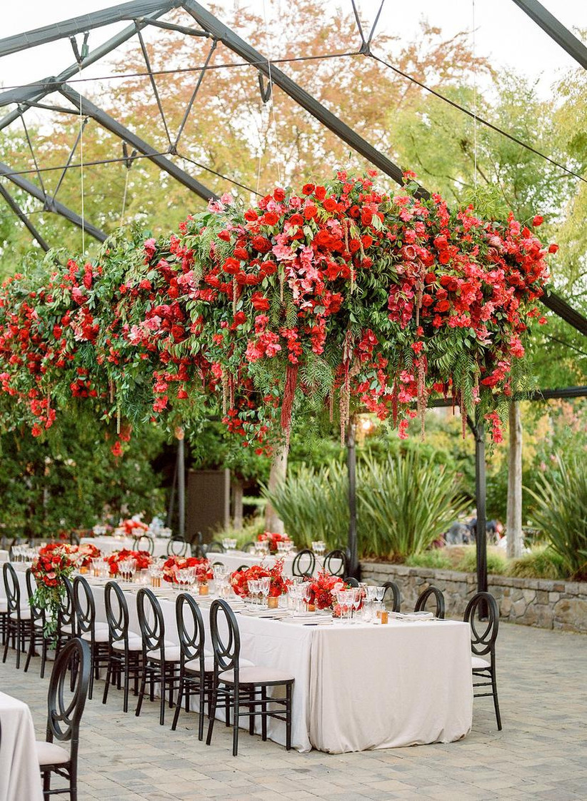 Red hanging flowers above a wedding table