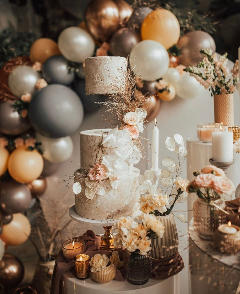Floating wedding cake stand surrounded by flowers, balloons and candles