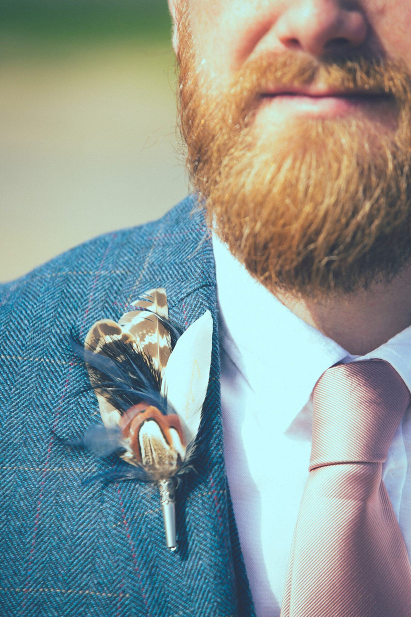 Groom wearing a feather wedding buttonhole