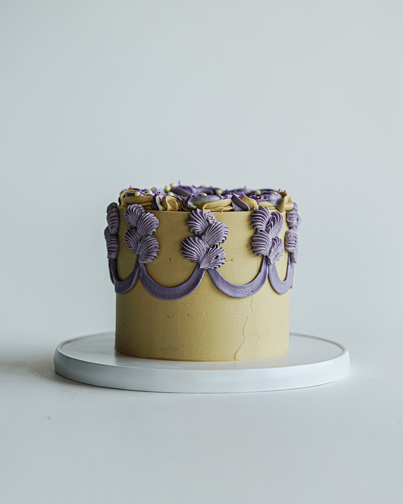 Yellow and purple cake with shell piping