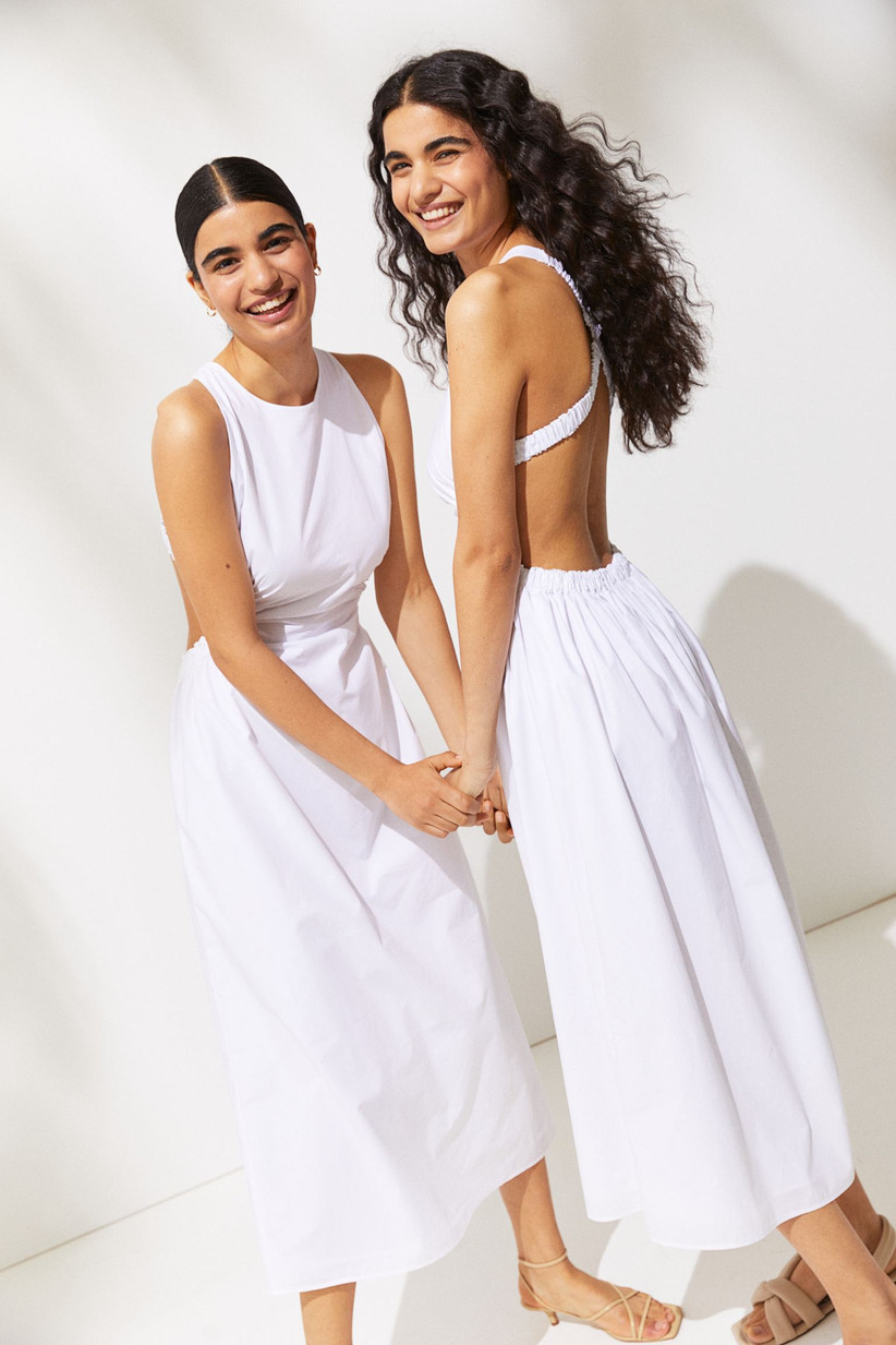 Two models wearing white cut out bridesmaid dresses
