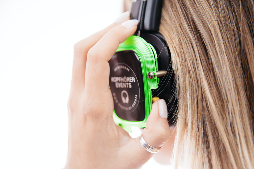 White woman with blonde hair wearing a pair of silent disco headphones
