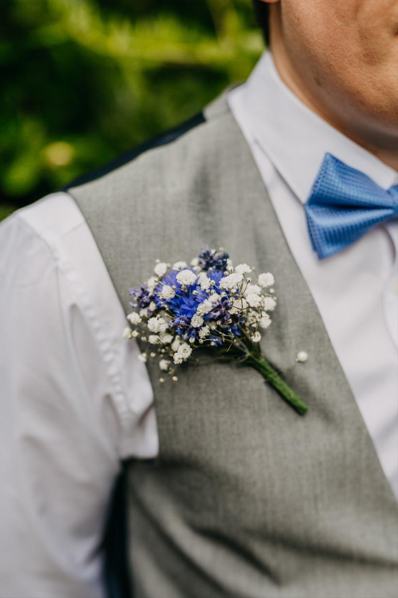 Groom wearing a cornflower wedding buttonhole
