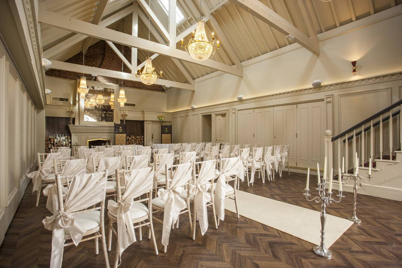 Rustic barn style wedding ceremony with white wooden beams