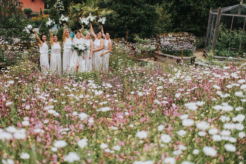 Bridal party put their bouquets in the air in a flower filled garden