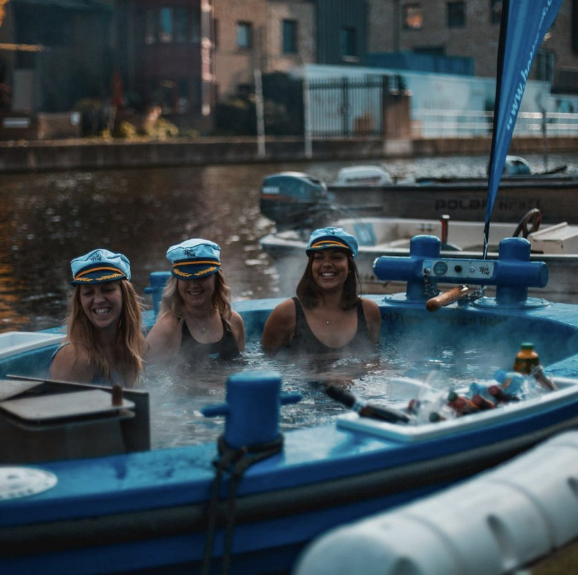 Three women in sailor hats and black swimming costumes laughing in a blue hot tub boat sailing down the Thames