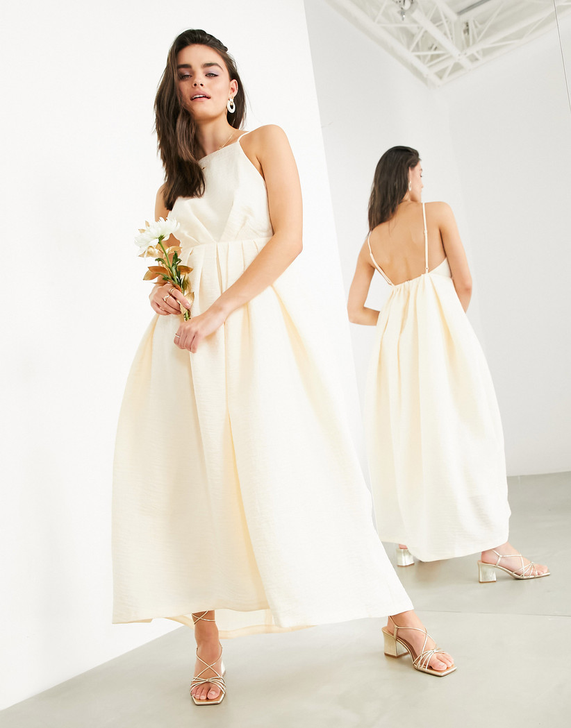 Model in a maxi apricot wedding dress holding flowers