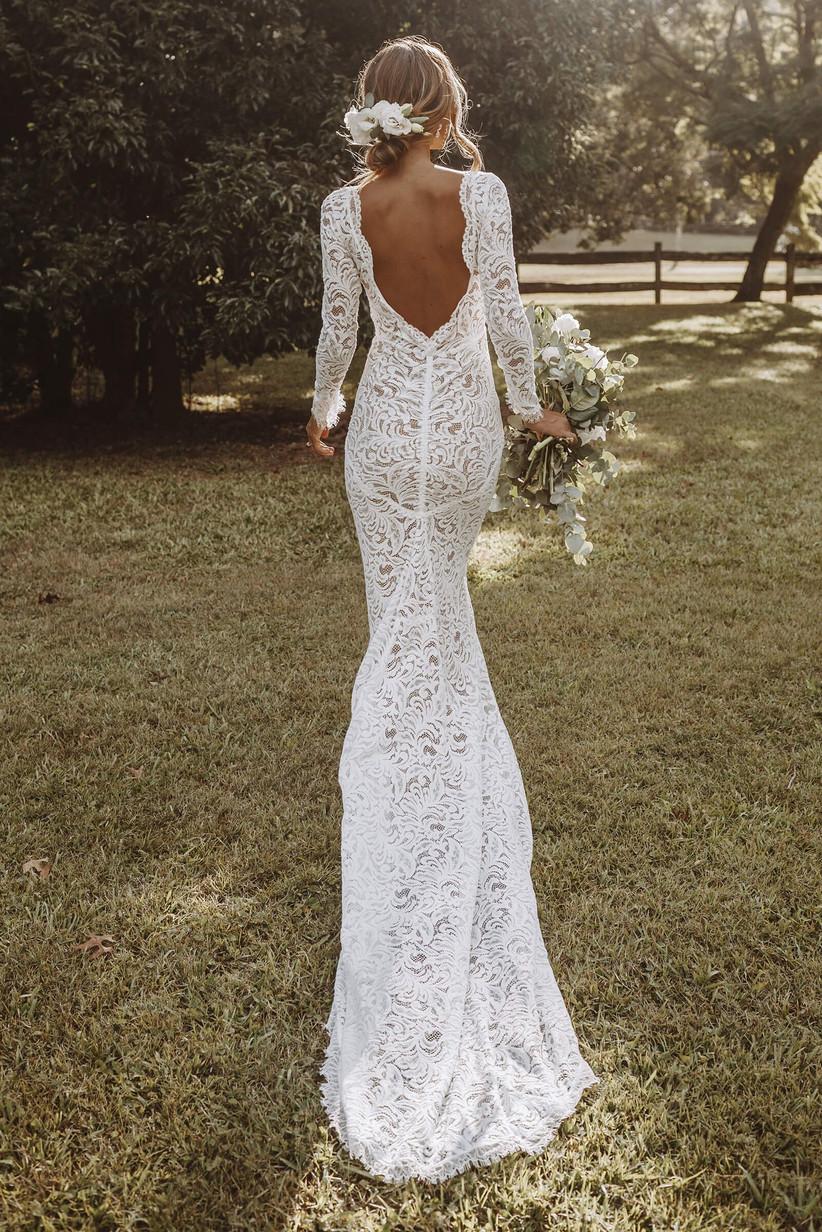 Model wearing a low back lace long sleeved wedding dress