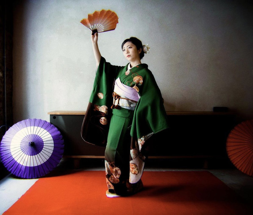 Japanese woman holding a fan above her head wearing a rich green kimono with a light pink belt standing on a red carpet